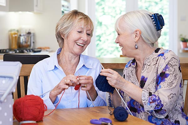 AgeBetter Connect: two women knitting at a table laughing